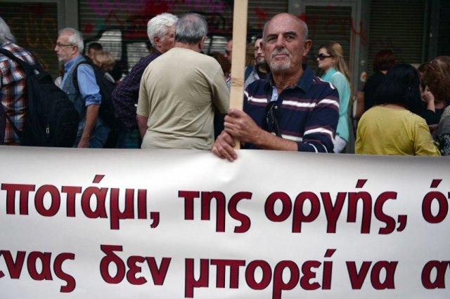 Ein Demonstrant steht hinter einem Anti-Austeritäts-Banner, während Beschäftigte des Öffentlichen Dienstes und Rentner am 21. October in Athen vor dem Arbeitsministerium protestieren. Die Gläubiger Griechenlands konferierten mit dem Finanzminister Euclid Tsakalotos. AFP PHOTO / LOUISA GOULIAMAKI